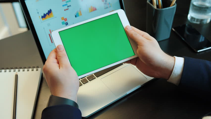 young man hands using tablet with green screan on the laptop backgroud with diagrams chroma