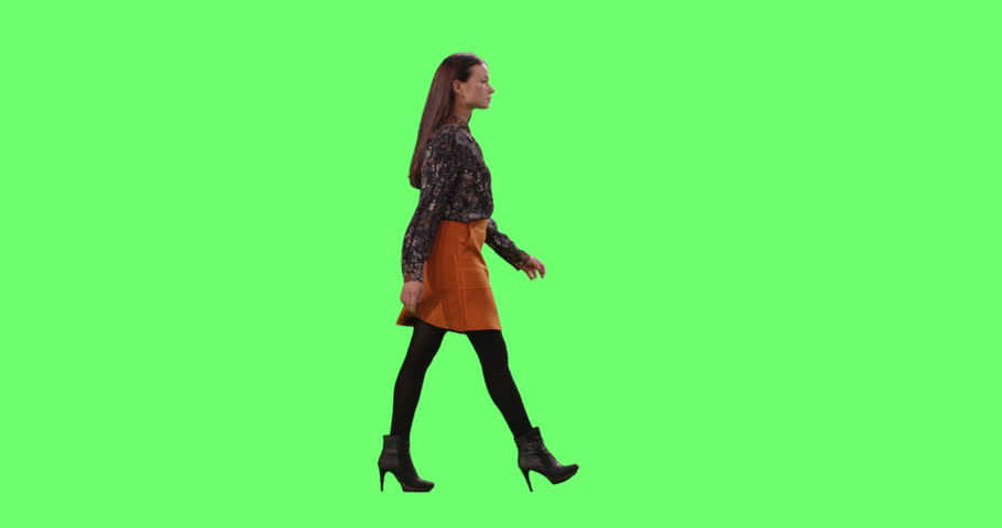 Stylish Young Brunette Gracefully Walking. Shot on a Mock-up Green Screen in the Background. Shot on RED Cinema Camera in 4K (UHD).