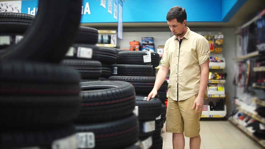 The car enthusiast choosing tires in the mall for his car. Man looking carefully on protector. Pile of tiers on background.