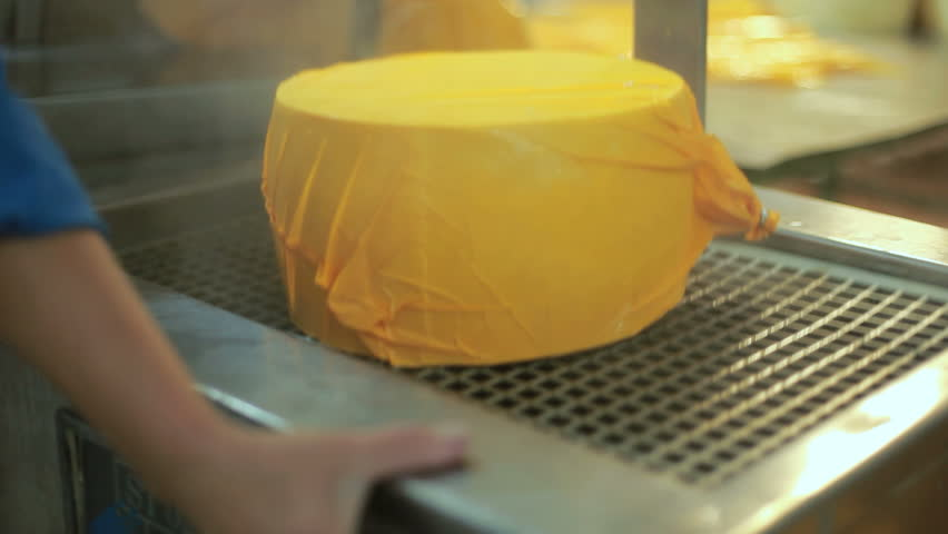 Cheese packaging process. Close up of cheese processing at food factory. Production food. Cheese factory manufacturing process. Cheese wheel on manufacturing line at food plant