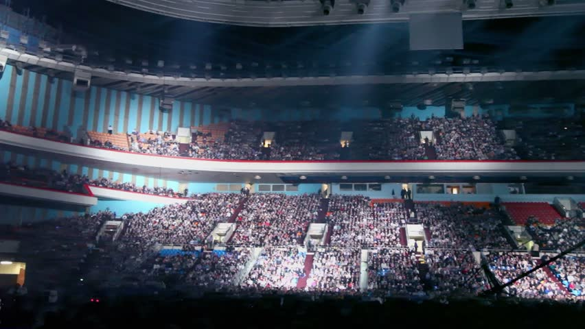 Searchlights in huge sports complex with lot of people on tribunes at concert, panoramic motion