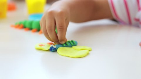 Young attractive mother with cute little daughter play with modeling clay at light living room. Mom and baby girl doing models of butterfly and caterpillar by plasticine.
