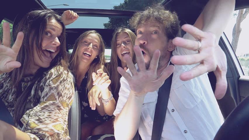 Happy beautiful family full of energy dancing in car slow motion looking camera medium shot