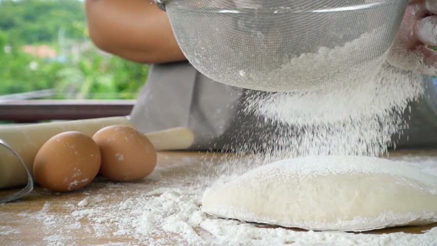 Close-up of flour through a metal sieve fray in green nature blur background. Ingredients and preparation stages. Slowmotion shot #28645654