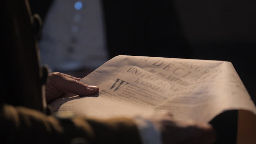 VIRGINIA - SUMMER 2016 - Reenactment, Founding Fathers, American Revolutionary War recreation -- Man reading document, Declaration of Independence to group in Tavern in 1700s.  Gentleman with group