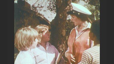 1970s: Children talk to crossing guard. Crossing guard smiles and talks. Children leave. Crossing guard waves. Crossing guard looks both ways and crosses street.