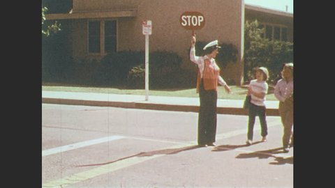 1970s: Crossing guard holds up Stop sign. 3 children cross street. Crossing guard talks to children.