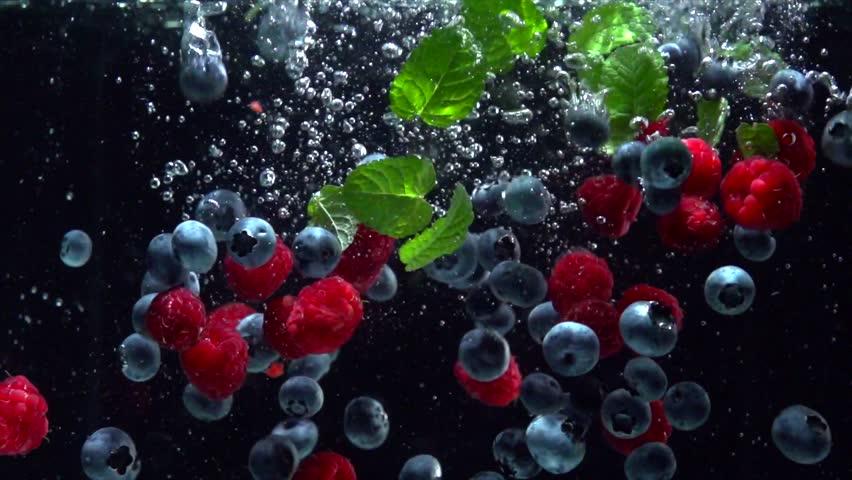 Raspberries, Blueberries and fresh mint leaves splashing into water on black background. Falling fresh fruits and berries in water. Organic berry, healthy food, diet 4K UHD video 3840X2160 slow motion