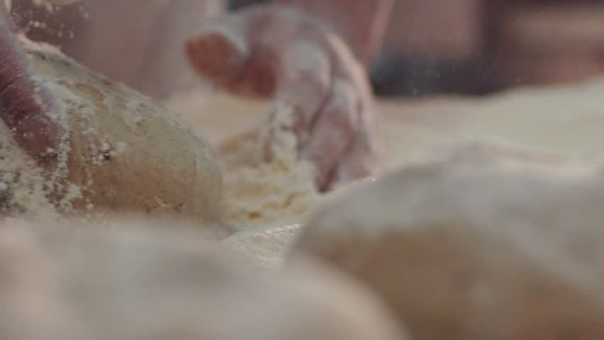 Extreme close up view of baker's hands one by one kneading the pieces of dough in the flour on the table. Beautiful process, daily routine. Baking manufacture, traditions. Bread-making industry.