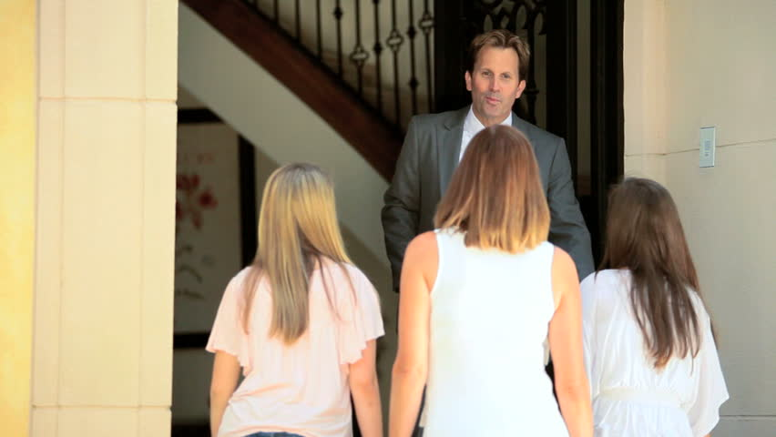 Successful Caucasian real estate agent greeting potential buyers on doorstep luxury home