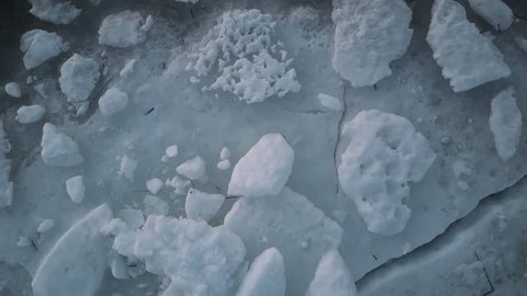 Aerial View Flight over the melting ice of the Northern Gulf The Frozen Finnish Gulf and shore in Melting Ice. Outstanding Scenery aerial view over rocky coast, highway and railway