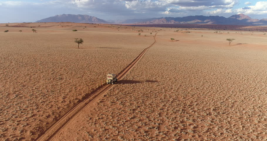 Aerial view of a safari vehicle driving through the vast plains of the NamibRand Nature Reserve, Namibia