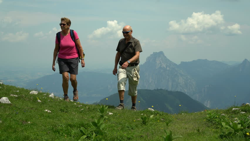 4k travel video, healthy fit active senior couple hiking hiking up beautiful mountain meadow high up in austrian alps