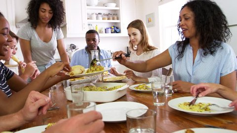 Two Families With Teenage Children Eating Meal In Kitchen