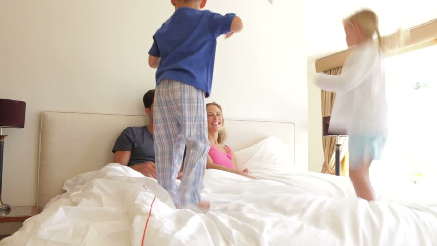 Boy and girl jumping on parents bed.