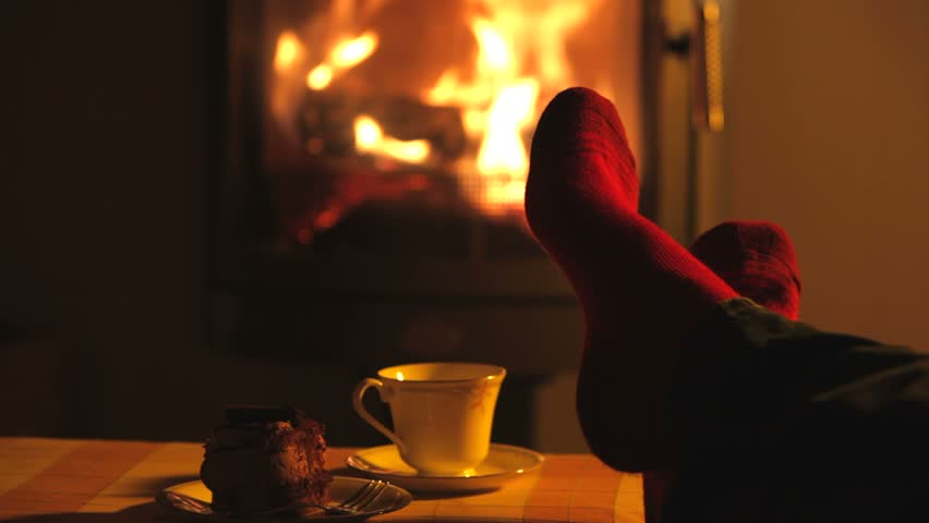 Man relaxes by warm fire and wriggles his toes.