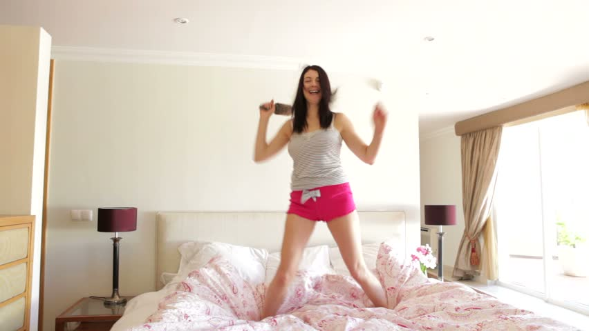 "Woman jumping on bed singing into hairbrush ""microphone"". 