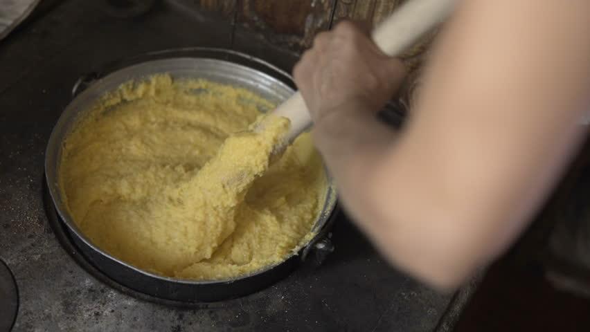 Woman preparing polenta on a firewood stove