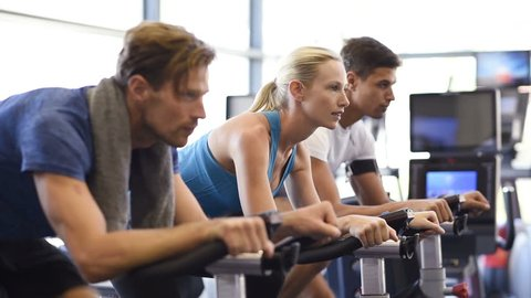 Fitness happy woman on stationary bicycle doing spinning at gym. Fit young woman working out on bike with man. Smiling girl exercising with group of people and looking at camera.