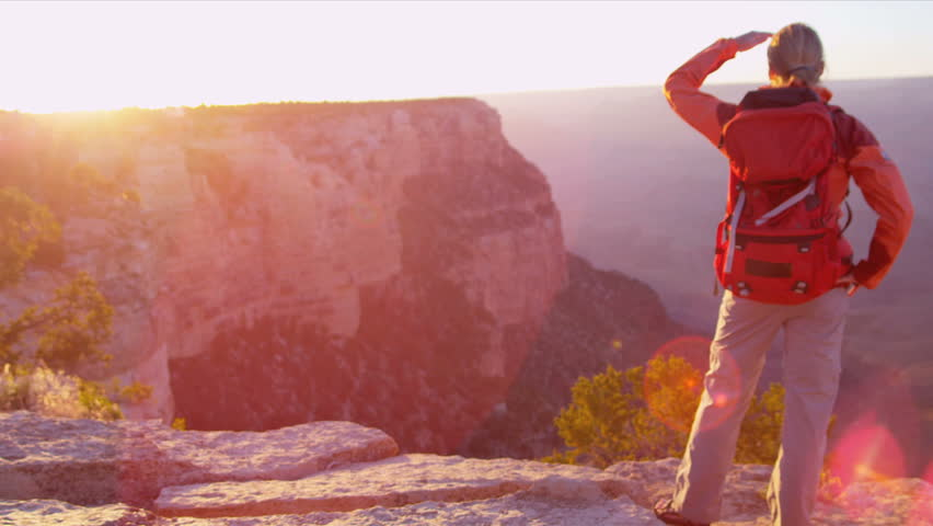 Lone female hiker watching the sun setting over the canyons, USA, Shot on Red Epic | Shutterstock HD Video #2877613