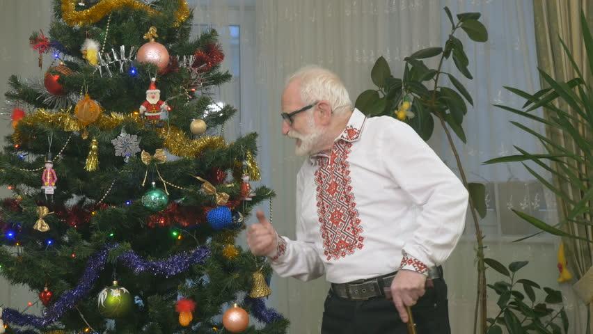 Old cheerful man dances near the christmas tree