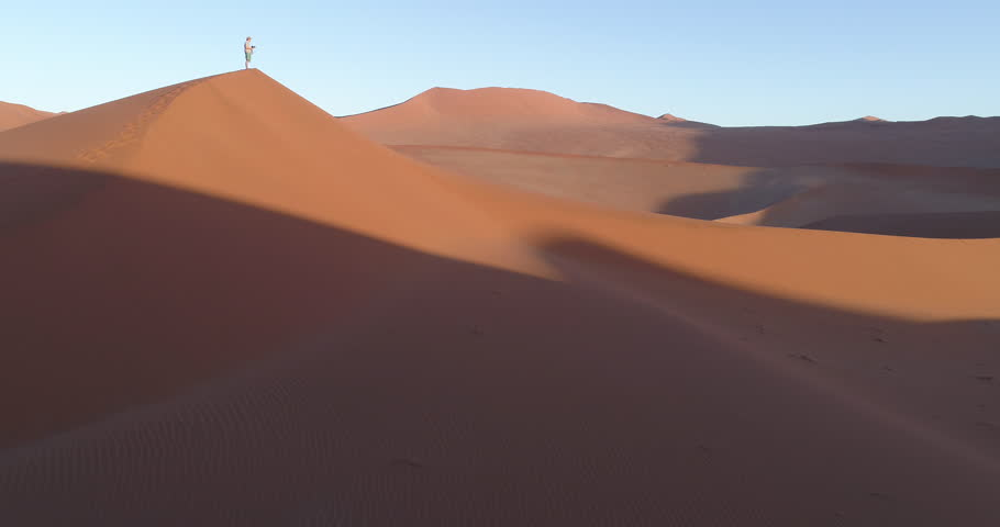 Tilt up aerial view of male tourist taking walking down one of the vast sand dunes in the Namib desert   Shutterstock HD Video #28779601