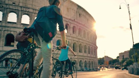Tourist Friends with bicycles riding in front of Colosseum in Rome