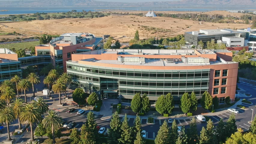 07 July, 2017., AERIAL flying over the Google HQ Googleplex and white google buses dropping off employees, Silicon Valley, San Francisco