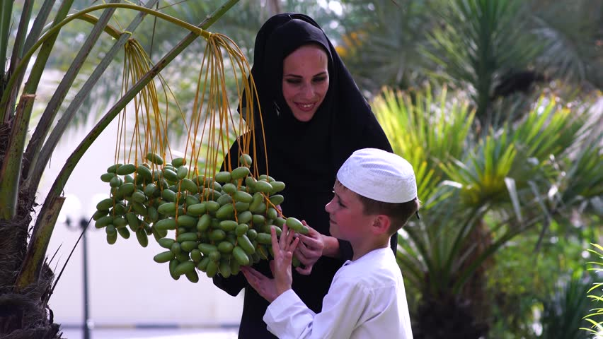 Arabic mother and son touching dates on tree.