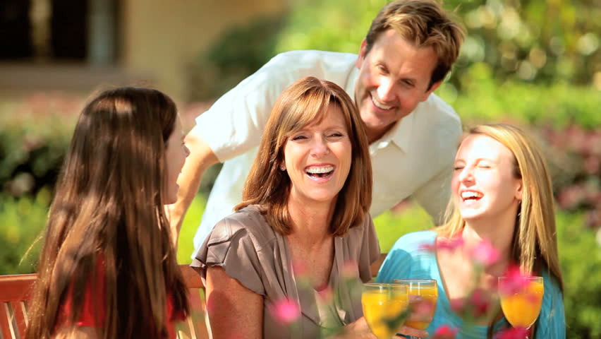 Caucasian parents spending time with teenage daughters outside home garden