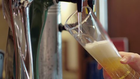 Beer is pouring from the top into the glass forming waves in bar
