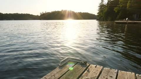 Slow motion shot of freshwater lake and sunshine with dock and cottages. Cottage country in Ontario, Canada.