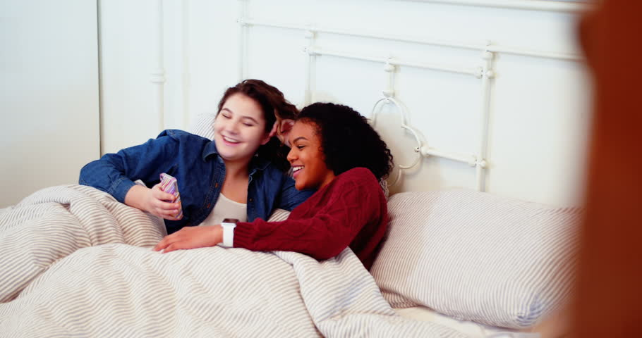 Lesbian couple having fun on their bed