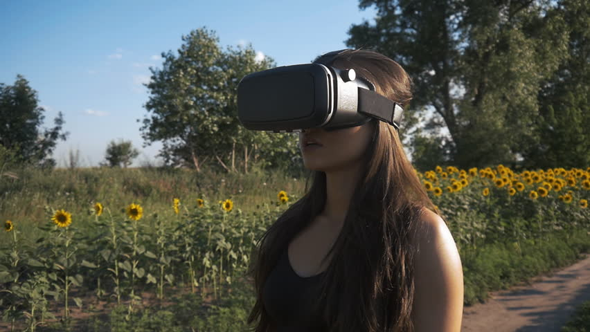 Young woman uses head-mounted display outdoor. Playing game using VR-helmet for smart phones. | Shutterstock HD Video #28953913