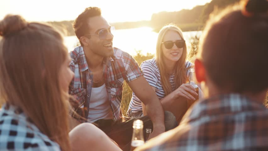 A company of four young friends having a picnic by the river, they are chatting, laughing, drinking beer. Casual wear, summertime, bright light of the sunset. Being happy, young and free. | Shutterstock HD Video #28972513
