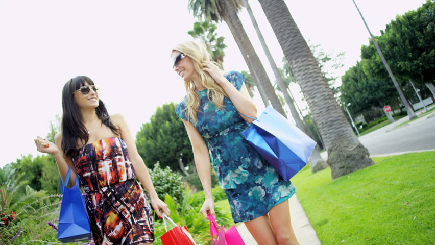 Beautiful young European girl friends in sunglasses and summer dresses carrying shopping bags and chatting happily   | Shutterstock HD Video #28983643
