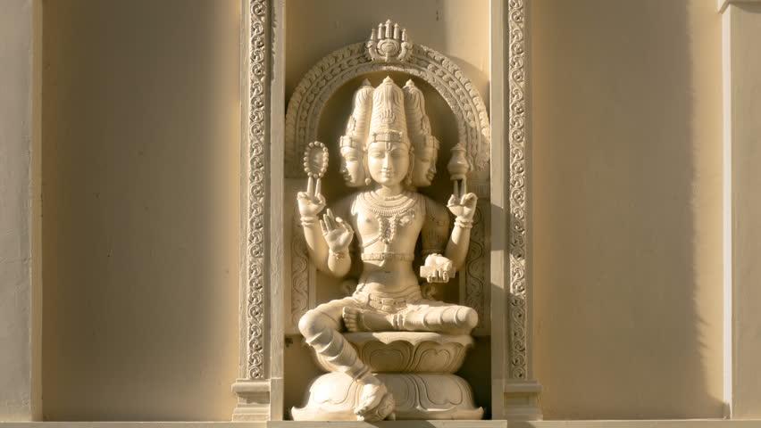 Hindu deity Brahma closeup on old temple wall time lapse