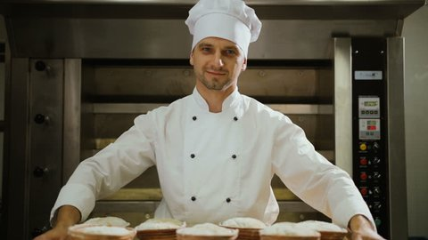 Portrait of smiling attractive worker in bakery shop with tasty bread.
