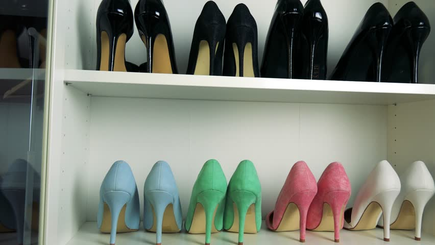 High heel shoes on shelves, the black ones on the top, the colorful ones on the bottom