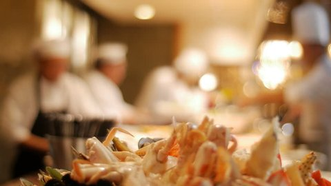 Seafood, plate of cooked steamed seafood with blurry background of chefs preparing food