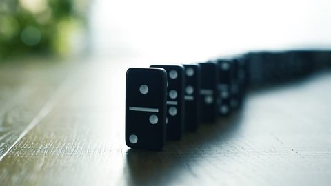 Male hand stopping domino effect and holding the tile with a finger: insurance, prevention and risk management concept
