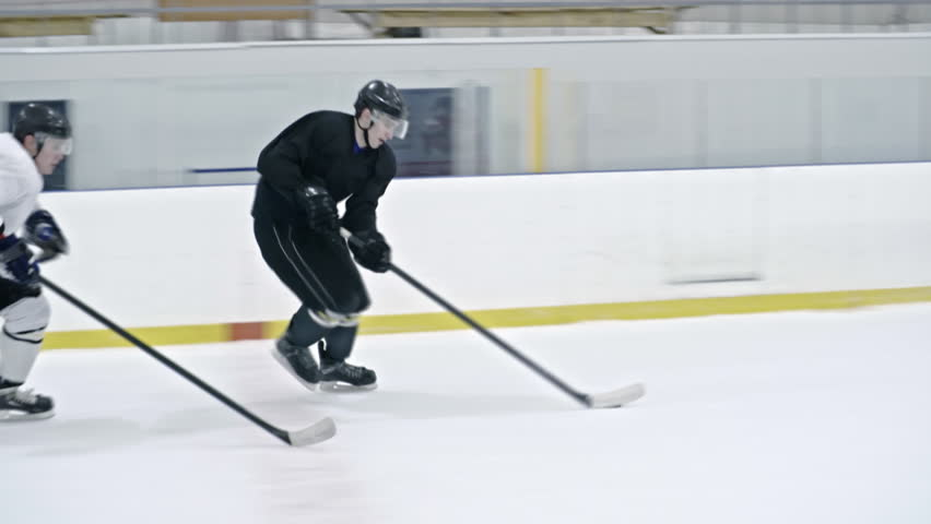Tracking of male ice hockey forward in black uniform dribbling puck and protecting it from opposite team players, then shooting it and scoring goal