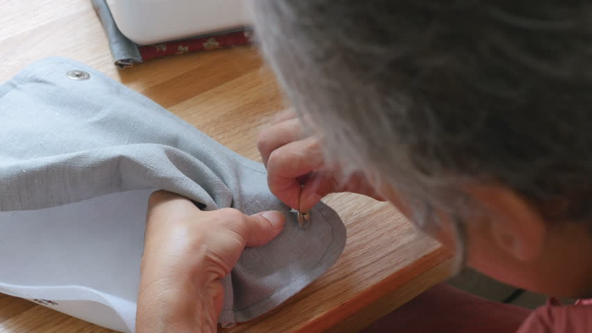 woman making handmade bag, she is adding buttons to the design in her studio, arts and crafts concept
