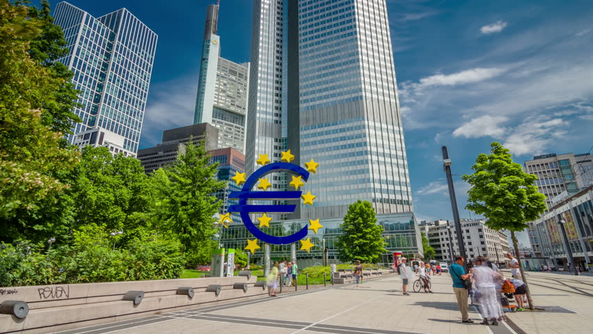 FRANKFURT AM MAIN, GERMANY - CIRCA JULI, 2017: Euro sign sculpture in a park among modern office towers and European Central Bank in Frankfurt, Germany. Hyperlapse/Timelapse view 4K.