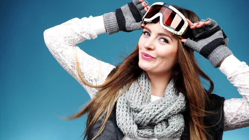 b1c138e16f Woman smiling skier girl wearing warm clothing ski goggles portrait. Winter  sport activity. Beautiful long hair sportswoman on blue studio shot