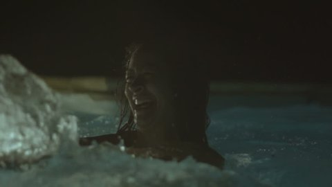 Young ladies enjoying in the swimming pool, in the night, slowmotion