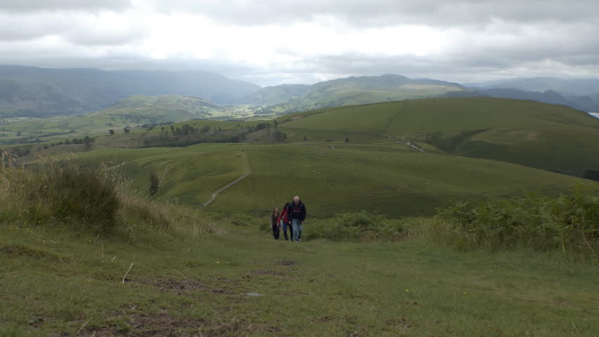 Front view of group of four people, one man and three women climbing up green hill in the English Lake District near Keswick, Cumbria, England, United Kingdom