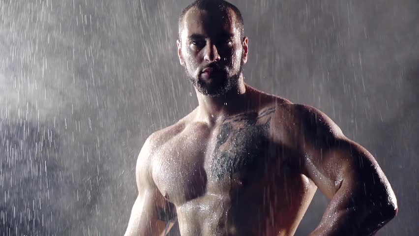 Nude man with big muscles chest shoulder back and arms. he stands under heavy rain in the night and thought