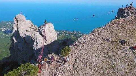 People Walking on a Suspension Bridge. Popular Russian Touristic Mountains Ai-Petri, Crimea. Extreme Footage. Black Sea Coast and Yalta City on Backgroung. HD Aerial