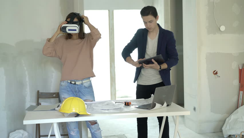 Mother and son with vr goggle and tablet watching virtual project at new home